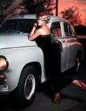 塑造摆在老汽车附近的减速火箭的样式的女孩 库存图片