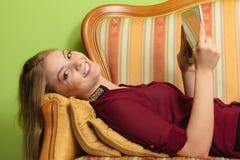塑造放置在有个人计算机片剂的沙发的妇女 库存照片