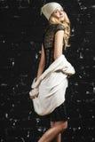 塑造时髦女孩画象有金发的,穿站立对黑都市墙壁的一件黑礼服和夹克 免版税库存照片
