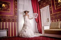 塑造时髦照片有卷发的美丽的新娘在与珍贵完善的姿势的一套华美的婚礼礼服在令人惊讶的内部 免版税库存图片