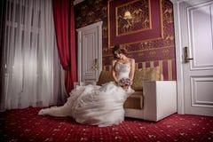 塑造时髦照片有卷发的美丽的新娘在与珍贵完善的姿势的一套华美的婚礼礼服在令人惊讶的内部 免版税图库摄影