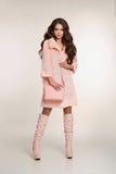 塑造时髦的女人照片桃红色外套的有提包wea的 库存照片