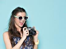 塑造时髦的妇女跳舞和制造照片使用减速火箭的照相机 在蓝色背景的画象在白色毛线衣 免版税库存图片