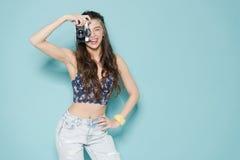 塑造时髦的妇女跳舞和制造照片使用减速火箭的照相机 在蓝色背景的画象在白色毛线衣 库存照片