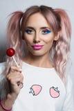 塑造有两桃红色马尾辫发型的女孩吃五颜六色的棒棒糖的 免版税库存照片