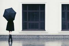 塑造有伞的妇女走在城市街道的 免版税库存照片