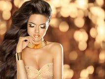 塑造有佩带在金黄犹太人的长的波浪发的美丽的女孩 免版税库存图片