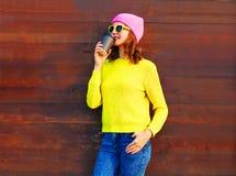 塑造有咖啡杯的凉快的女孩在穿桃红色帽子黄色毛线衣的木背景的五颜六色的衣裳 库存图片