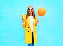 塑造有橙色气球和杯子的相当微笑的妇女果汁 免版税图库摄影