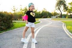 塑造有滑板佩带的小女孩孩子太阳镜和行家衬衣 库存照片