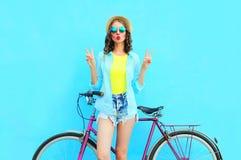 塑造有自行车的俏丽的妇女在五颜六色的蓝色backgroun 免版税库存照片