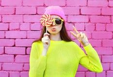 塑造有获得的棒棒糖的画象相当凉快的女孩在五颜六色的桃红色的乐趣 免版税库存图片