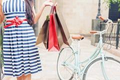塑造有袋子的妇女并且骑自行车,购物的旅行到意大利 库存图片