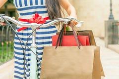 塑造有袋子的妇女并且骑自行车,购物的旅行到意大利 免版税图库摄影