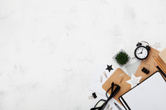 塑造有镜片的博客作者运转的书桌,办公用品,闹钟并且清洗笔记本顶视图 平的位置样式 复制空间 免版税库存图片
