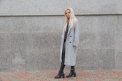 塑造样式灰色皮大衣的年轻端庄的妇女走在城市街道的 库存图片