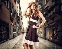 塑造棕色礼服和帽子的妇女在白色 免版税库存照片