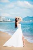 塑造步行沿着向下在一件白色礼服的沿海的新娘 美丽的女孩走赤足下来海滩 衣物夫妇日愉快的葡萄酒婚礼 库存照片