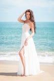 塑造步行沿着向下在一件白色礼服的海滩的新娘 美丽的女孩走赤足下来海滩 免版税库存照片