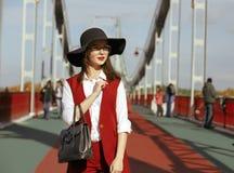 塑造深色的模型画象在红色服装和黑帽会议的 图库摄影