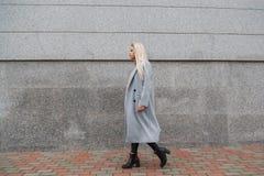 塑造灰色皮大衣的走在城市街道的年轻美丽的端庄的妇女样式画象  图库摄影