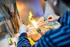 塑造热的玻璃的艺术家在有气体的一个小雕象 库存照片