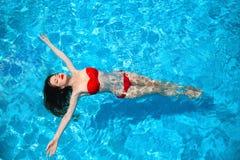塑造田园诗性感的比基尼泳装表面上的被晒黑的妇女游泳  免版税图库摄影