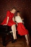 塑造白种人芭蕾舞女演员坐钢琴和笑 库存照片