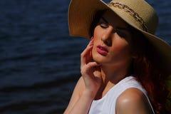 塑造白色礼服和魅力帽子的妇女户外在河岸,在背景的深大海 库存照片