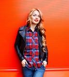 塑造相当佩带在五颜六色的红色的年轻白肤金发的妇女一个黑岩石样式 免版税库存照片