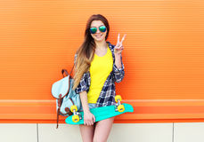 塑造相当凉快女孩佩带太阳镜,有获得的滑板的背包乐趣 免版税库存图片