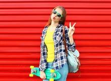 塑造相当凉快女孩佩带太阳镜,滑板 免版税库存照片