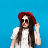 塑造相当吹红色lipswearing的黑帽会议太阳镜和红色帽子的少妇 免版税图库摄影