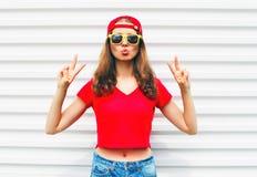 塑造相当太阳镜和红色T恤杉的凉快的妇女在白色 库存照片