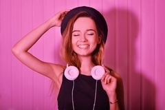 塑造相当帽子和耳机的凉快的妇女听到在桃红色霓虹背景的音乐的 帽子的美丽的年轻十几岁的女孩 库存图片