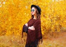 塑造相当微笑的妇女模型佩带的黑帽会议太阳镜和被编织的雨披在秋天黄色叶子 库存照片