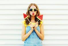 塑造相当有两切片的凉快的女孩西瓜吹她的嘴唇的冰淇凌 免版税图库摄影