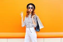塑造相当有穿在五颜六色的桔子的购物袋的凉快的女孩黑帽会议白色裤子 免版税库存图片