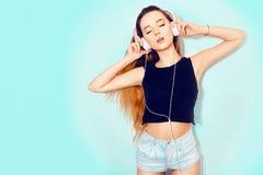 塑造相当耳机的凉快的妇女听到在蓝色背景的音乐的 有长的头发的美丽的年轻十几岁的女孩 舞蹈 库存图片