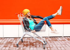 塑造相当戴在五颜六色的桔子的台车推车的凉快的女孩黑夹克帽子 免版税图库摄影