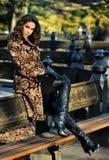 塑造秋天摆在公园的美丽的妇女室外照片 库存图片