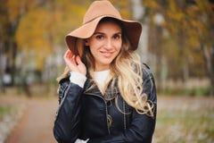 塑造秋天画象年轻愉快妇女走室外在秋天公园 免版税库存照片