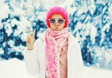 塑造穿五颜六色的被编织的帽子围巾的冬天少妇获得乐趣 免版税图库摄影