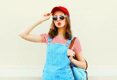 塑造穿有棒球帽和太阳镜的年轻俏丽的妇女一条牛仔布连衫裤在白色 免版税库存图片