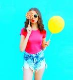 塑造穿桃红色T恤杉,与黄色气球,在五颜六色的蓝色的棒棒糖糖果的牛仔布短裤的画象相当少妇 库存照片