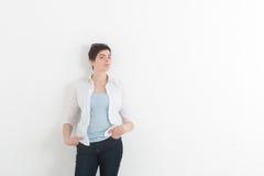 塑造穿深蓝牛仔裤和白色衬衣有太阳镜的少妇在斜眼看她的头看对照相机和 免版税图库摄影