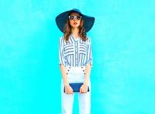 塑造穿草帽,有一台提包传动器的白色裤子的少妇在摆在城市的五颜六色的蓝色背景 库存图片