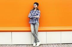 塑造穿黑帽会议、太阳镜和衬衣在五颜六色的桔子的俏丽的妇女 免版税库存图片