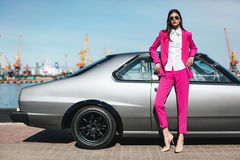 塑造站立在一辆减速火箭的跑车旁边的女孩 免版税图库摄影