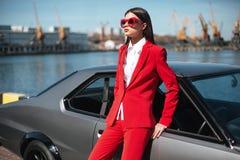 塑造站立在太阳的一辆减速火箭的跑车旁边的女孩 等待在经典汽车附近的一套红色衣服和太阳镜的时髦的妇女 库存照片